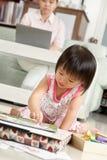 女孩她的演奏工作的小母亲 免版税库存照片