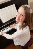 女孩她的演奏微笑的钢琴 免版税库存图片