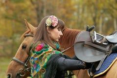 女孩她的马备鞍的年轻人 库存照片