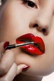 女孩她的嘴唇油漆 免版税图库摄影