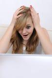 女孩她膝上型计算机凝视惊奇的少年 库存照片
