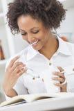 黑女孩妇女读书&饮用的咖啡 库存照片