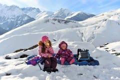 女孩姐妹在山的冬天旅行 免版税库存图片
