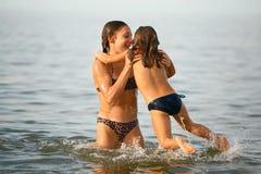 女孩姐妹获得沐浴在海的乐趣 免版税库存照片