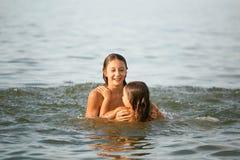 女孩姐妹获得沐浴在海的乐趣 库存图片
