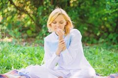 女孩嫩白肤金发的嗅微小的花,当坐绿草草甸时 纯净和嫩概念 妇女享用放松自然 图库摄影