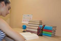 女孩学习 执行女孩她的家庭作业 在书桌,教育概念上的教科书 免版税库存照片