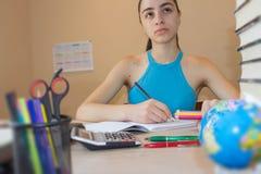 女孩学习 执行女孩她的家庭作业 在书桌,教育概念上的教科书 库存照片