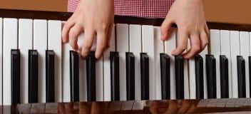 女孩学会弹钢琴 免版税库存照片