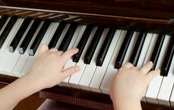 女孩学会弹钢琴 免版税图库摄影
