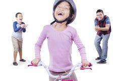 女孩学会骑有爸爸和兄弟的一辆自行车 免版税库存照片