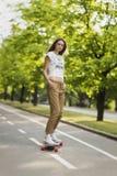 女孩学生模型气喘衬衣,并且运动鞋在b乘坐 库存图片