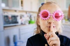女孩学龄前儿童投入了手指到嘴唇 免版税图库摄影