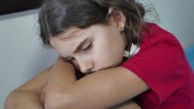 女孩孩子儿童站立在床上的墙壁拥抱膝盖接受户内她自己附近的悲伤寂寞消沉 股票录像