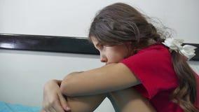 女孩孩子儿童站立在床上的墙壁拥抱膝盖附近的悲伤寂寞接受消沉户内她自己 股票录像