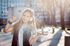 女孩孩子听到从她的智能手机的音乐 免版税库存照片