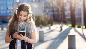 女孩孩子听到从她的智能手机的音乐 免版税库存图片