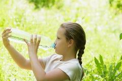 女孩孩子喝从室外的瓶的水 免版税库存照片