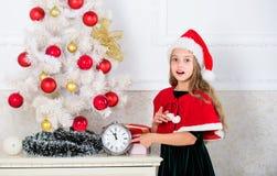 女孩孩子圣诞老人有计数时间的时钟的帽子服装对新年 以前多少时刻 最后一刻直到半夜12点 新 图库摄影