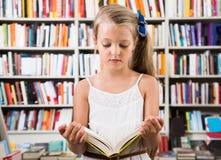 女孩孩子在书店考虑书 免版税库存图片