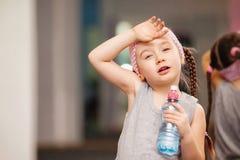 女孩孩子在健身俱乐部,饮料水的训练健身锻炼以后是疲乏 免版税库存图片