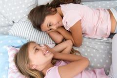 女孩孩子在床放置有逗人喜爱的枕头顶视图 睡衣派对概念 有乐趣的女孩 诚实少女的秘密 库存图片