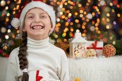 女孩孩子在有圣诞节礼物的圣诞老人帽子穿戴了在黑暗被阐明的背景、新年好和冬天庆祝概念 免版税库存照片