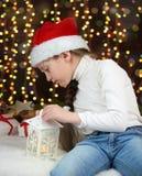 女孩孩子在有圣诞节礼物的圣诞老人帽子穿戴了在黑暗被阐明的背景、新年好和冬天庆祝概念 库存照片