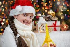 女孩孩子在有埃佛尔铁塔玩具的圣诞老人帽子穿戴了,并且在黑暗的圣诞节礼物阐明了背景、新年好和winte 免版税库存照片