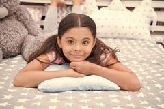 ?? 女孩孩子在枕头放置在她的卧室 孩子准备上床 宜人的时间时髦的内部 ?? 库存图片