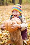 女孩孩子在秋天森林里用南瓜和苹果,在秋季的美好的风景与黄色叶子 库存照片