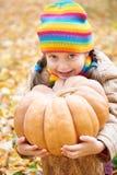女孩孩子在秋天森林里用南瓜和苹果,在秋季的美好的风景与黄色叶子 免版税库存照片