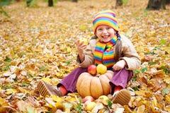 女孩孩子在秋天森林里用南瓜和苹果,在秋季的美好的风景与黄色叶子 免版税图库摄影