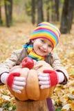 女孩孩子在秋天森林里用南瓜和苹果,在秋季的美好的风景与黄色叶子 免版税库存图片