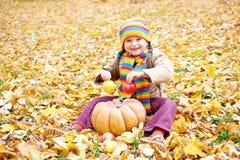 女孩孩子在秋天森林,坐黄色叶子,吃苹果和南瓜 免版税库存图片
