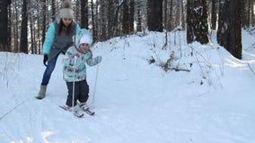 女孩孩子学会滑雪 她在软的新鲜的雪的滑雪慢慢地滑 在冬天森林妇女的美好的天 股票视频