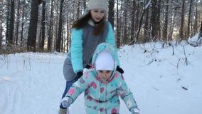 女孩孩子学会滑雪 她在软的新鲜的雪的滑雪慢慢地滑 在冬天森林妇女的美好的天 股票录像