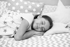 女孩孩子睡着在枕头 睡眠的质量取决于许多因素 选择适当的枕头很好睡觉 女孩位置 免版税图库摄影