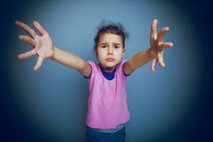 女孩孩子请求在灰色背景的手 库存图片