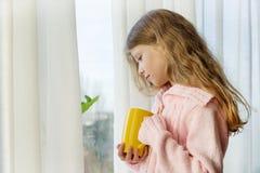 女孩孩子7岁白肤金发与在一件温暖的被编织的毛线衣的长的波浪发在窗口拿着一杯茶并且看 库存图片