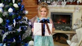 女孩孩子给有礼物的,圣诞节的一件礼物,有一件礼物的一个逗人喜爱的小女孩一个箱子在a附近的手立场 股票录像