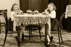 女孩孪生饮用的茶在一张古色古香的桌上与鞋带tablecl 库存图片