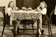 女孩孪生饮用的茶在一张古色古香的桌上与鞋带tablecl 免版税库存照片
