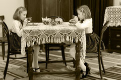 女孩孪生饮用的茶在一张古色古香的桌上与鞋带tablecl 库存照片