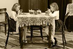 女孩孪生饮用的茶在一张古色古香的桌上与鞋带tablecl 免版税库存图片