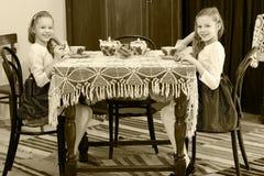 女孩孪生饮用的茶在一张古色古香的桌上与鞋带tablecl 图库摄影