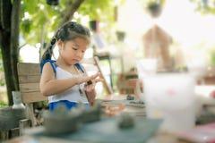 女孩实践的模子瓦器工作的黏土作为爱好 免版税库存照片