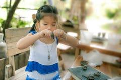 女孩实践的模子瓦器工作的黏土作为爱好 库存照片