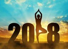 女孩实践的瑜伽在新年2018年 库存图片
