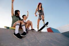 女孩实践的踩滑板与朋友欢呼 免版税库存图片